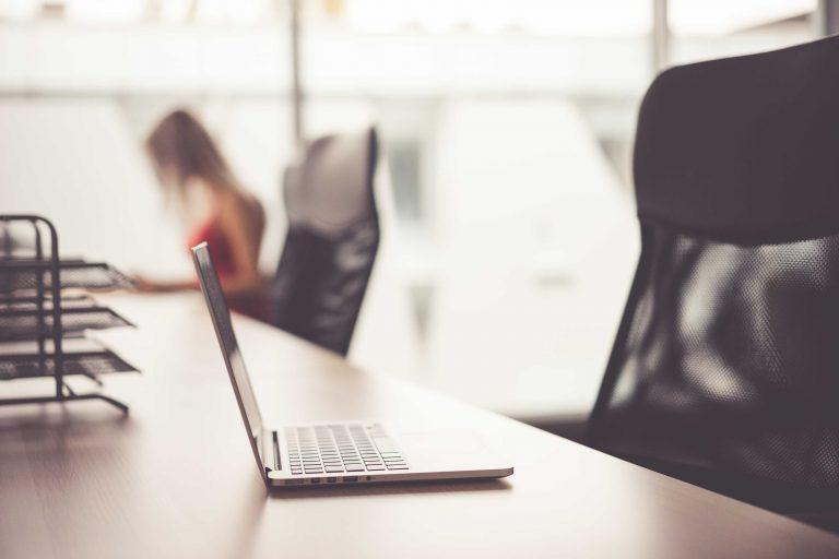 Laptop on Wooden Desk in Office Open Space